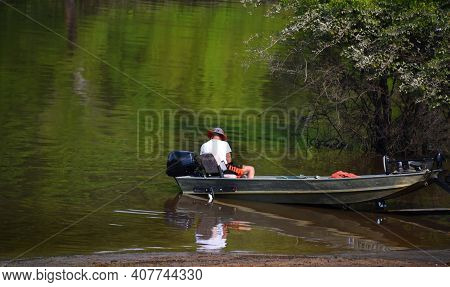 Man Readies His Boat As He Prepares For A Day Of Fishing The Ouachita River In Arkansas.  He Has On
