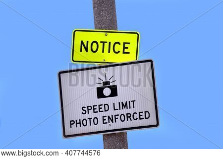 Sign Posted On Roadway States That Speed Limiot Is Photo Enforced.  Yellow Sign Above Calls Attentio