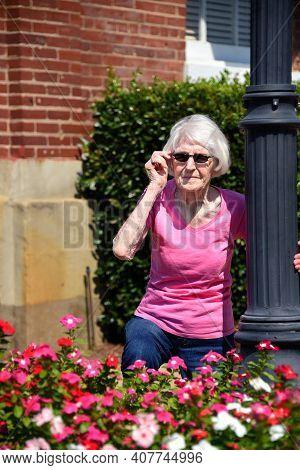 Adjusting Her Shades Senior Kneels By Flowers