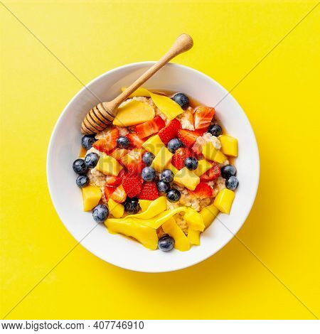 Tasty Appetizing Homemade Porridge With Fruits, Honey And Berries Served On Plate On Bright Yellow B
