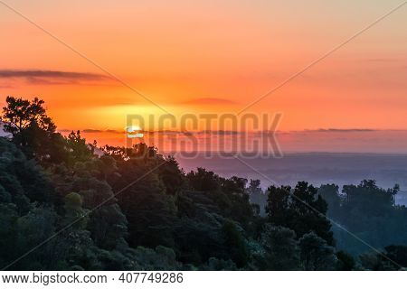 Sunset Over The Ocean With A Forest Foreground. Thin Cloud Cover With A Spectacular Sunflare