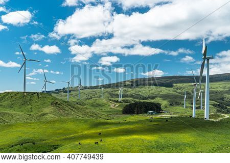 Wind Farm On A Beautiful Slightly Cloudy Day With A Meadow And Surrounded By Farmland.