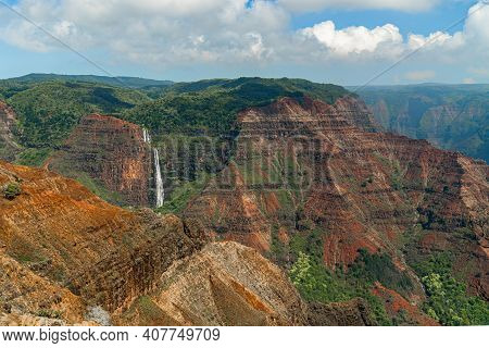 Waterfall In Waimea Canyon With Rich Orange And Green Landscape.