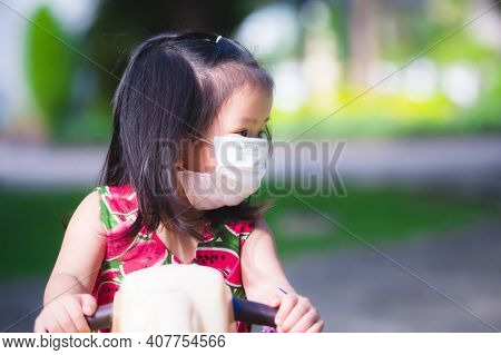Girl Play With Toys Rocking Horse In The Playground. Children Wear White Medical Face Masks Against