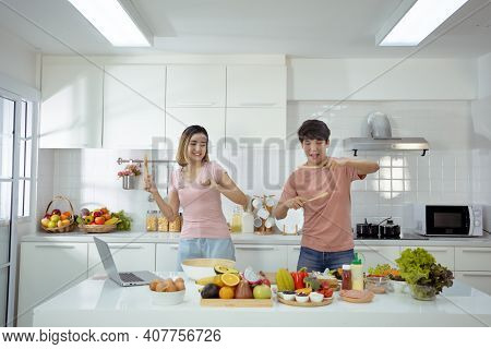 Couple Young Asian Dancing To Music Together Enjoying Cooking And Smile Enjoy Life Together In Home