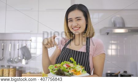 Young Asian Beautiful Smiling Woman Making Vegetable Salad In The Kitchen. Woman In Pink Shirt Stand