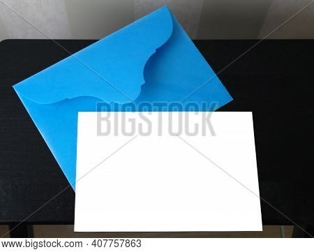 White Card In A Blue Envelope On A Black Table For Mocap, Copy Space