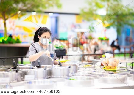 Asian Woman Wearing Mask Scooping Up Buffet Meals At The Time Of The Coronavirus (covid-19) Outbreak