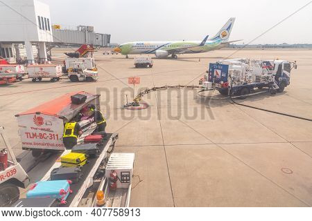 Bangkok, Thailand- January 24 2021 : Airline Crew Loads Checked Baggage Into Airplane Cargo And Refu