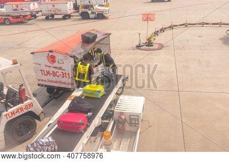 Bangkok, Thailand- January 24 2021 : Airline Crew Loads Checked Baggage Into Airplane Cargo At Don M