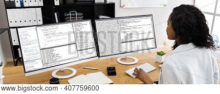 African Coder Using Multiple Computer Screens In Office
