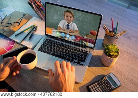 Caucasian schoolboy learning displayed on laptop screen during video call with male teacher. Online education staying at home in self isolation during quarantine lockdown.