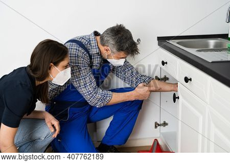 Kitchen Pipe Damage Problem. Woman And Repairman In Face Mask