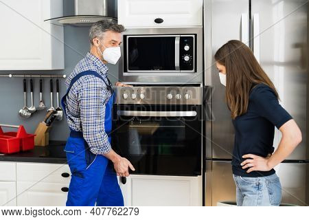 Oven Appliance Appliance In Kitchen By Handyman In Face Mask
