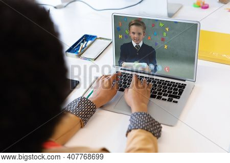 Mixed race female teacher using laptop on video call with schoolboy learning from home. Online education staying at home in self isolation during quarantine lockdown.