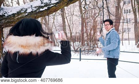 Young Happy Asian Couple Playing Winter Games. Snowball Fight. High Quality Photo