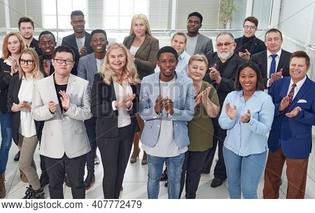 group of diverse corporate employees applauding together .