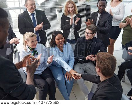 employees greeting their new colleague with applause.