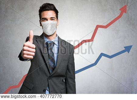 Masked business man giving thumbs up in front of a positive diagram during covid coronavirus pandemic