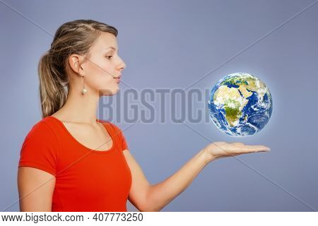 An image of a nice young woman watching planet earth above her hand