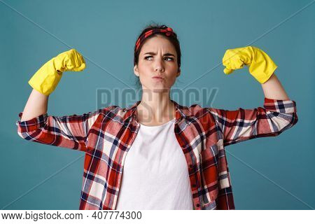 Perplexed caucasian young woman in gloves showing her biceps isolated over blue background