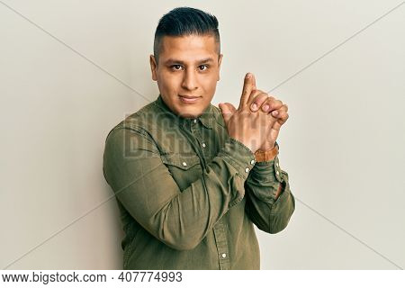 Young latin man wearing casual clothes holding symbolic gun with hand gesture, playing killing shooting weapons, angry face