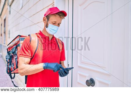 Caucasian delivery man wearing red uniform and delivery backpack and coronavirus safety mask using smartphone