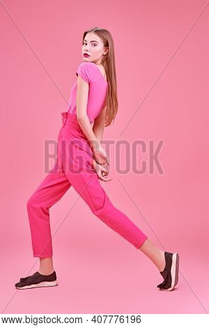 Beautiful girl fashion model poses at studio in trendy crimson suit on a pink background. Glamorous pink style. Full length portrait.