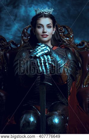 The Middle Ages history. Portrait of a beautiful medieval queen in knightly armor sitting on a throne and holding a sword.