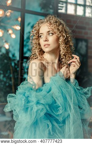 Elegant woman in a long vintage blue dress. Fabulous girl. Cover of a love story.