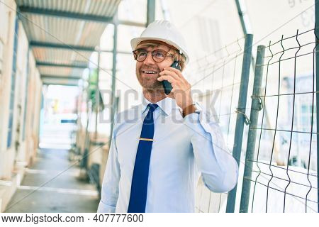 Business architect man wearing hardhat standing outdoors of a building project speaking on the phone