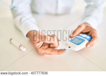 Close up of man with diabetes using insuline glucometer with blood from the finger