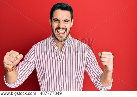Young hispanic man wearing business shirt screaming proud, celebrating victory and success very excited with raised arms