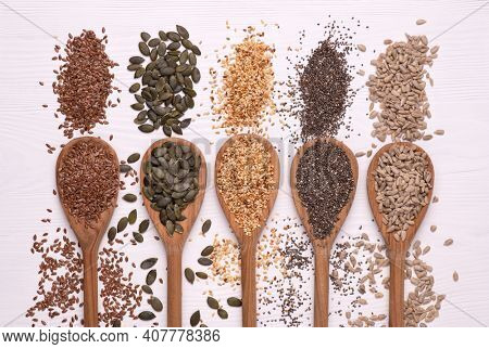 Healthy seeds - sesame, flax seed, sunflower seeds, pumpkin seed, chia in wooden spoons on a white background. Top view
