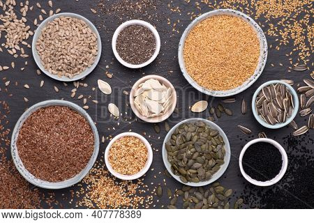 Healthy seeds - sesame, flax seed, sunflower seeds, pumpkin seed, chia and black seed in bowls on a black stone background. Top view