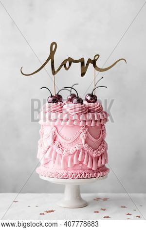 Vintage celebration cake with pastel pink vintage buttercream piping and banner with love