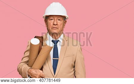 Senior caucasian man wearing safety helmet holding blueprints thinking attitude and sober expression looking self confident