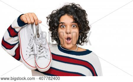 Young hispanic woman with curly hair holding white casual shoes scared and amazed with open mouth for surprise, disbelief face