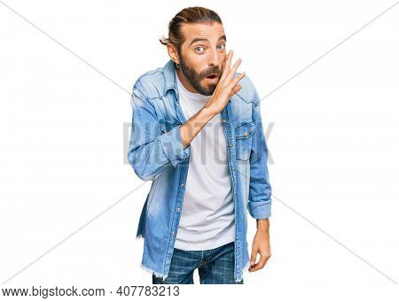 Attractive man with long hair and beard wearing casual denim jacket hand on mouth telling secret rumor, whispering malicious talk conversation