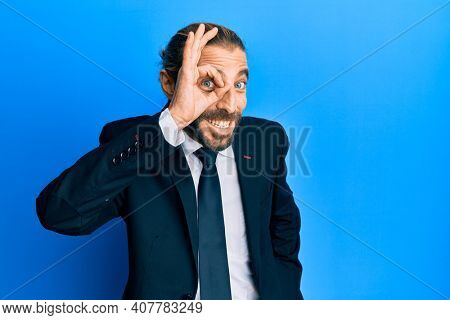 Attractive man with long hair and beard wearing business suit and tie smiling happy doing ok sign with hand on eye looking through fingers