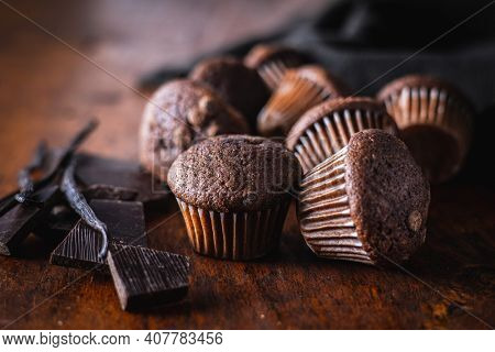 Chocolate muffins. Sweet dark cupcakes with chocolate and vanilla pods on wooden table.