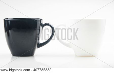 Mug mock up. Two ceramic mugs on white background. Blank coffee or tea mugs. Black cup and white cup. Copy space