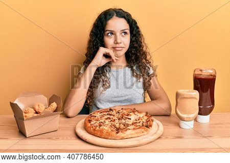 Teenager hispanic girl eating pizza and fried chicken thinking concentrated about doubt with finger on chin and looking up wondering