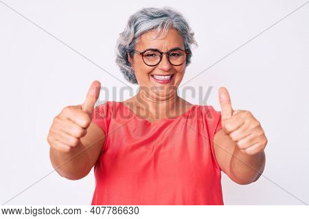 Senior hispanic grey- haired woman wearing casual clothes and glasses approving doing positive gesture with hand, thumbs up smiling and happy for success. winner gesture.