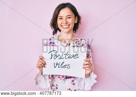 Young beautiful girl holding positive vibes banner smiling with a happy and cool smile on face. showing teeth.
