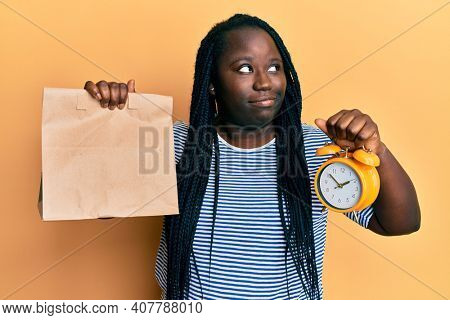 Young black woman with braids holding take away food and alarm clock smiling looking to the side and staring away thinking.