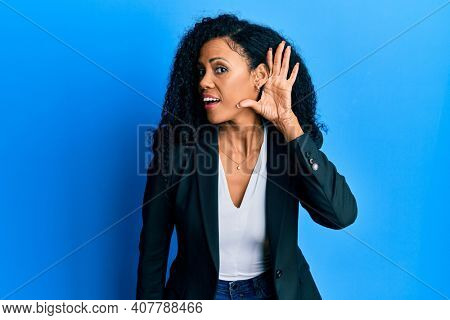 Middle age african american woman wearing business clothes smiling with hand over ear listening an hearing to rumor or gossip. deafness concept.