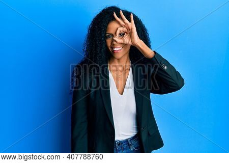 Middle age african american woman wearing business clothes doing ok gesture with hand smiling, eye looking through fingers with happy face.