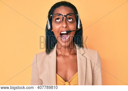 Young african american woman wearing call center agent headset angry and mad screaming frustrated and furious, shouting with anger looking up.