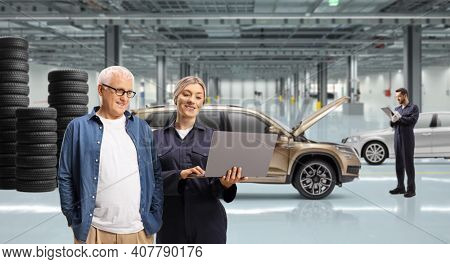 Mature man and a female auto mechanic looking at a laptop computer in a auto repair workshop